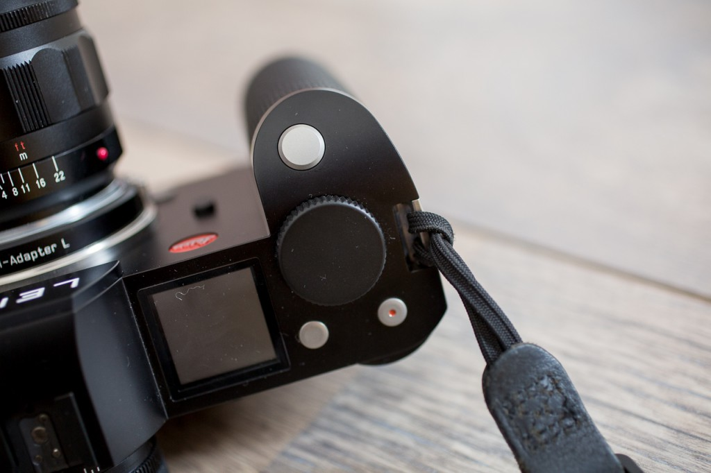 Keep it simple: nothing wrong with classic loops for attaching a camera strap.